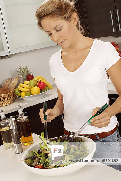 Woman In Kitchen Making Salad
