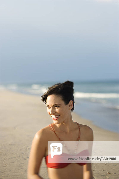 Caucasian mid-adult Female smiling am Strand in Badeanzug.