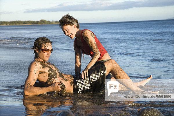 Caucasian erwachsen Paares herumtollen am Strand.