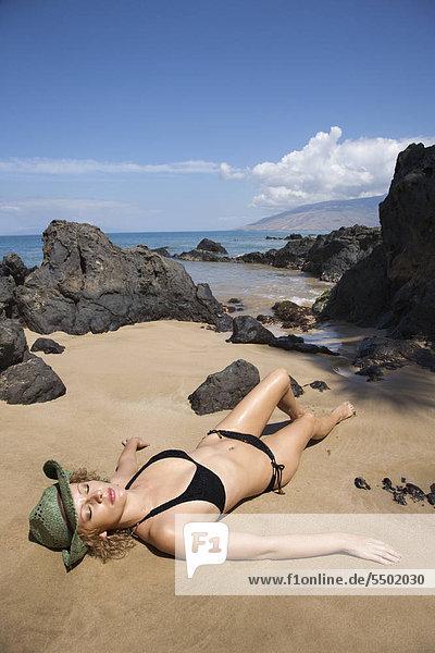 Porträt der jungen Erwachsenen weiblichen Caucasian im Bikini am Strand liegen.