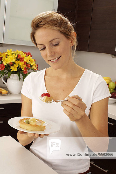 Woman In Kitchen Eating Fruit Pastry / Torte