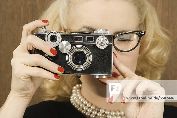 Mid-adult Caucasian female in vintage outfit holding a vintage film camera up to her face.