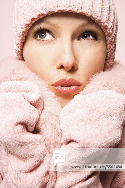 Caucasian mid-adult woman on pink background wearing winter coat and hat.