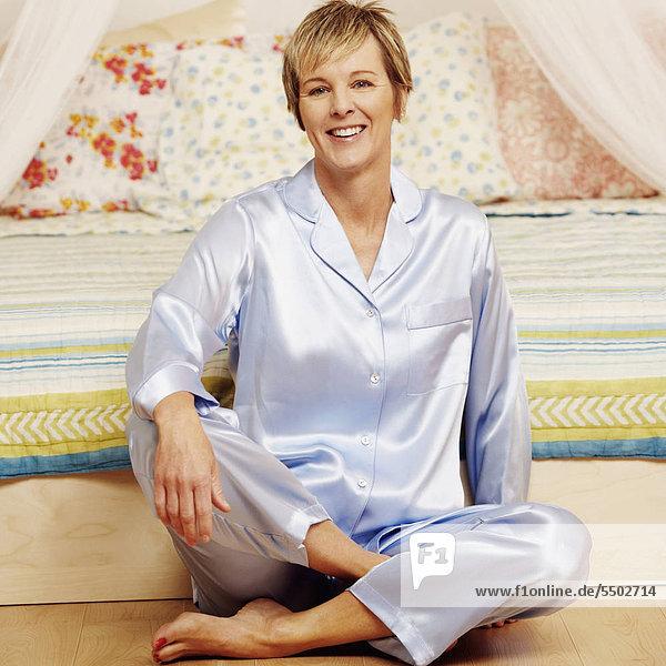 sitzend Portrait Frau Boden Fußboden Fußböden lächeln reifer Erwachsene reife Erwachsene