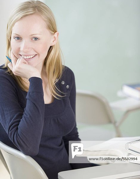 Woman sitting at Desk im Klassenzimmer