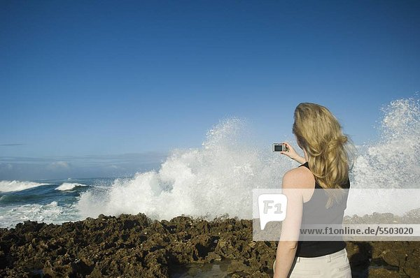 Woman taking photograph of ocean  Oahu  Hawaii  United States