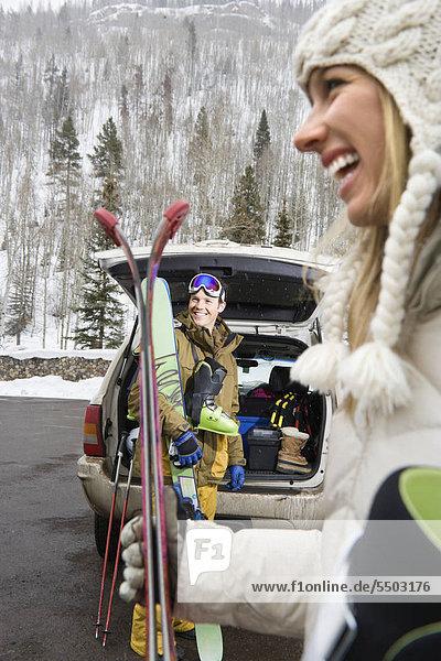 Couple Standing mit Ski-Ausrüstung von offenen Fahrzeug Lächeln und lachen.