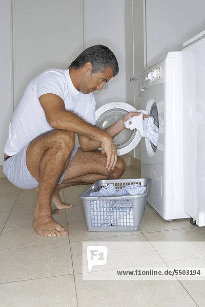 Mann sitzt vor der Waschmaschine