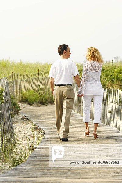 Rear view of a man and a woman walking on a boardwalk