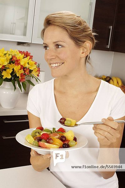 Woman In Kitchen Eating Obstsalat