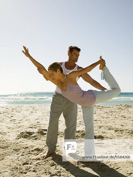 A man helping woman perform yoga on a beach.