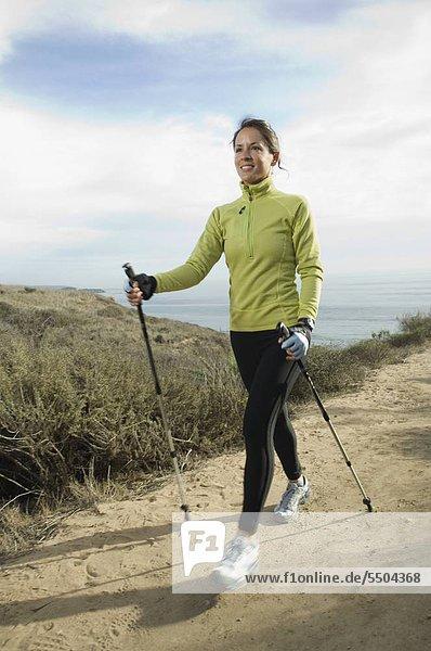 Hispanic woman pole walking along coast in California  United States