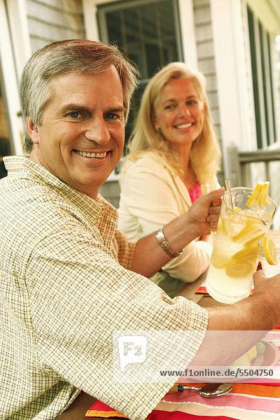 sitzend nebeneinander neben Seite an Seite Portrait Frau Mann Glas eingießen einschenken reifer Erwachsene reife Erwachsene Zitrusfrucht Zitrone Saft