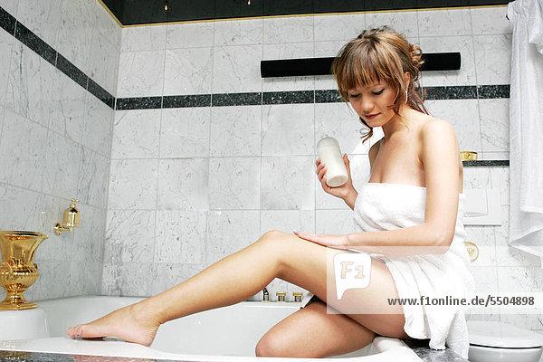 Junge Frau im Bad  Anwendung Körperlotion