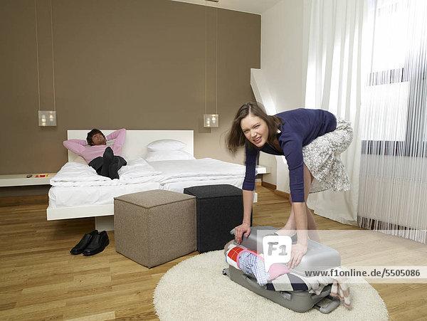 Frau packt Koffer  Mann auf Bett