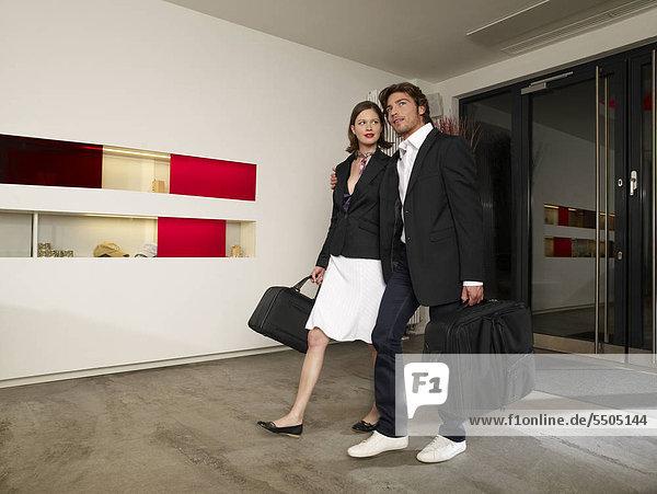 Junges Paar mit Gepäck im Hotel