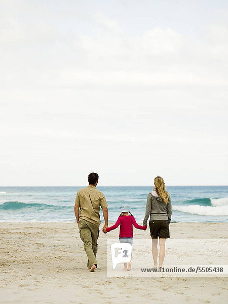 Parents walking on the beach with their daughter.