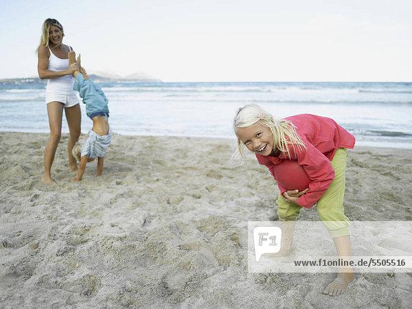 Mutter spielt mit Kindern am Strand