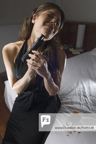 Junge Frau setzt sich Pistole an die Kehle