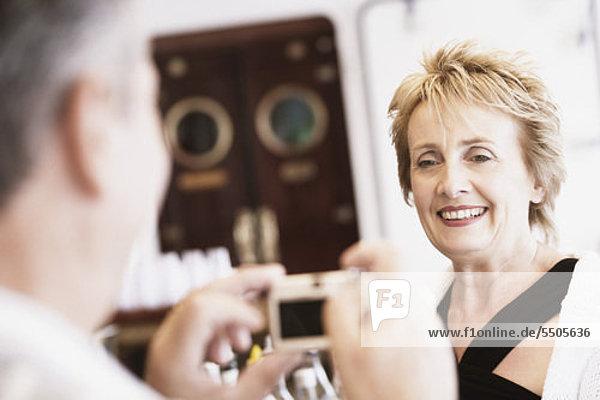 älterer Mann ein Bild von einer Frau mit einer Digitalkamera nehmen und lächelnd
