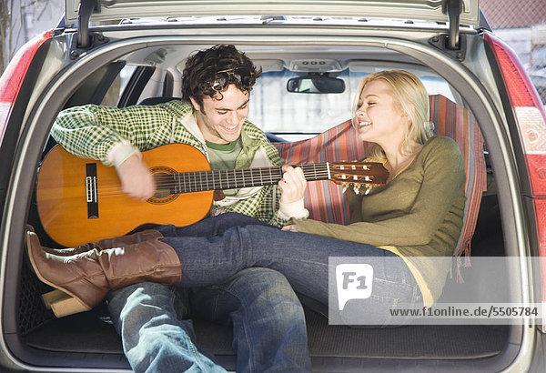 Paar sitzen auf der Rückseite des Autos mit Gitarre