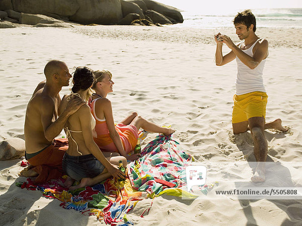 Man photographing his friends on the beach.