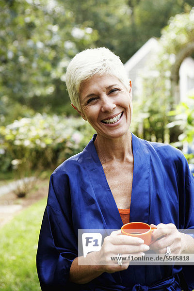 Portrait of a senior woman holding a cup of tea and smiling