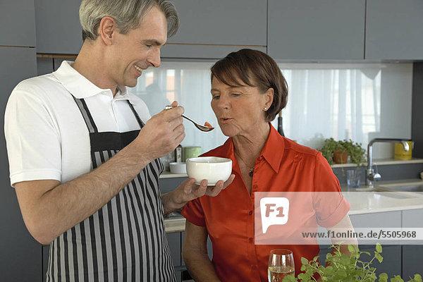 Älteres Paar beim Naschen in der Küche