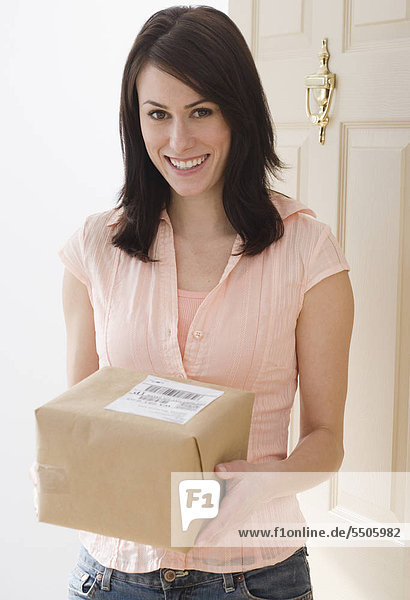 Portrait of Woman holding Paket im Eingang