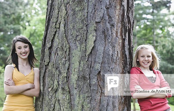 Girls leaning against large tree