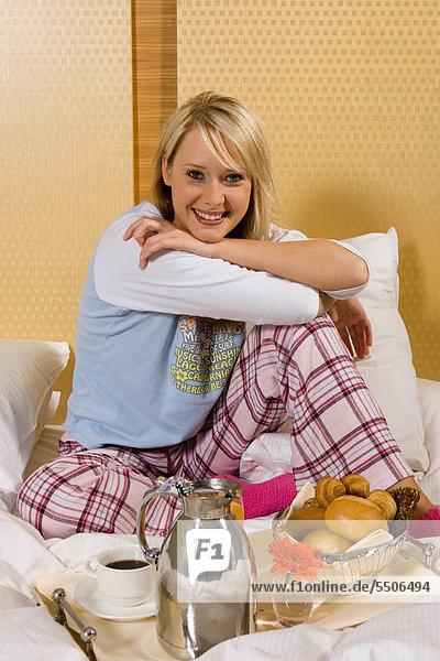 Junges Mädchen mit Frühstück im Bett in ihren Pyjamas