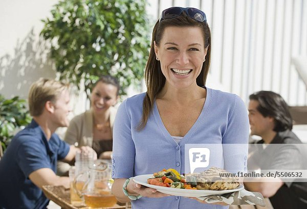 Portrait of woman dining on patio with friends