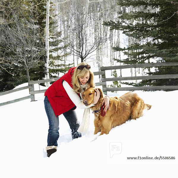 Woman with Arms um Hund im Schnee bedeckt Colorado Landschaft.
