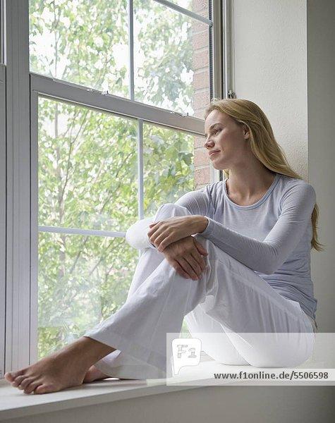 Woman sitting on Fensterbank aus Fenster Suchen