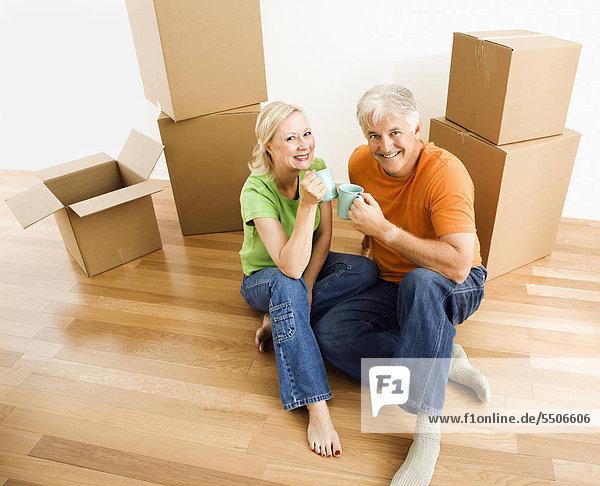 zwischen inmitten mitten sitzend reifer Erwachsene reife Erwachsene Boden Fußboden Fußböden Bewegung Kaffee Pappschachtel Pappkarton Pappe