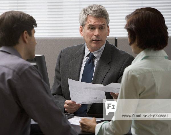 Kaufmann im Gespräch mit Paar im Büro