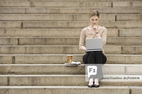 Young Woman sitting im Freien auf Treppe mit laptop