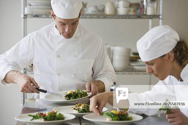 Männliche und weibliche Köche Beschichtung Essen
