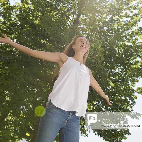 Frau mit ausgestreckten stehen unter Baum