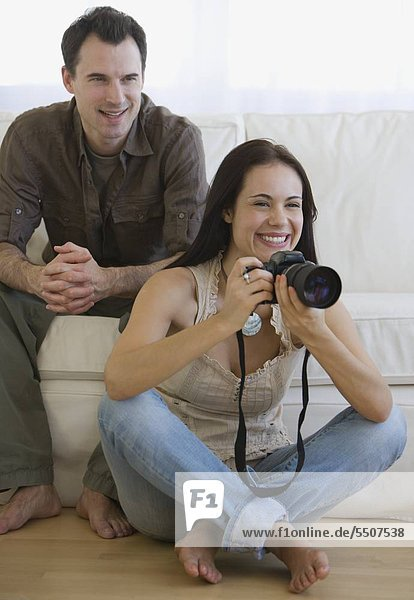 Woman holding camera next to face