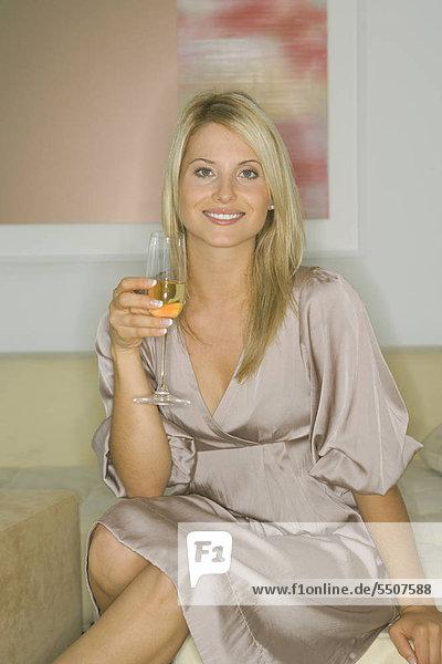 Junge Frau trinkt ein Glas Sekt