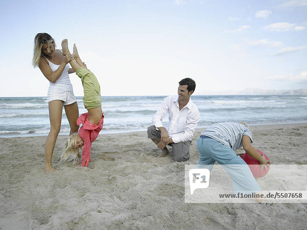 Mid adult couple and their children playing on the beach