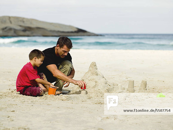 Father and son building sand castles on the beach.