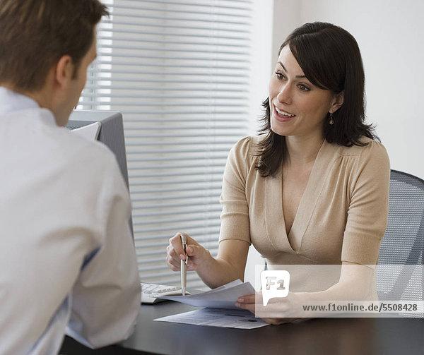 Geschäftsfrau Gespräch mit Mitarbeiter am Schreibtisch