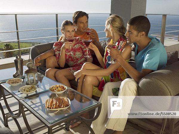 Junge Leute feiern auf der Dachterrasse am Meer und trinken Cocktails