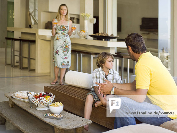 Eltern unterhalten sich mit ihrem Sohn im Wohnzimmer