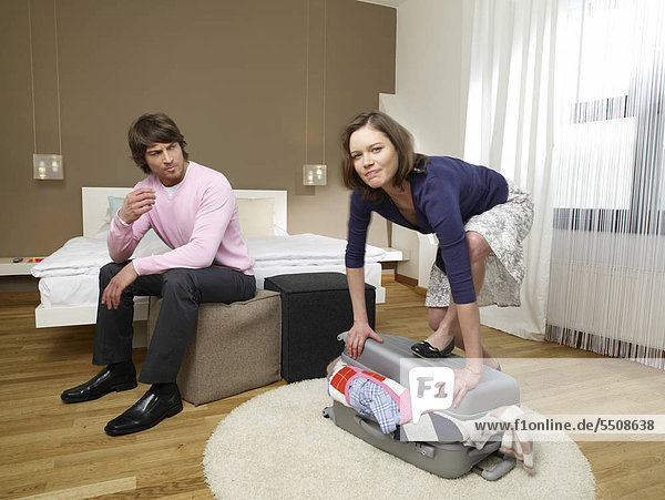 Man looking at his girlfriend shutting a suitcase.
