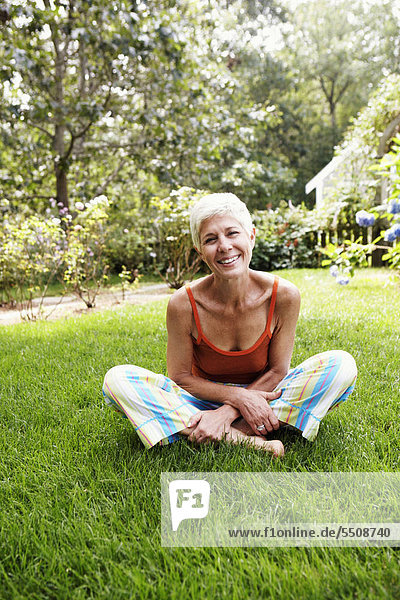 Portrait of a senior woman sitting on grass and smiling