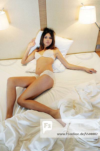 liegend liegen liegt liegendes liegender liegende daliegen Frau Bett Unterwäsche jung dunkelhaarig