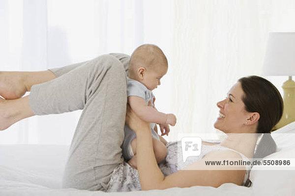 Mutter spielen mit Baby auf dem Bett